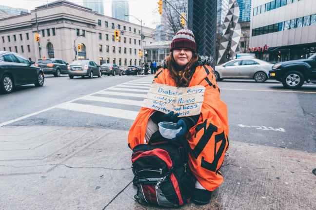 photo of woman sitting on sidewalk